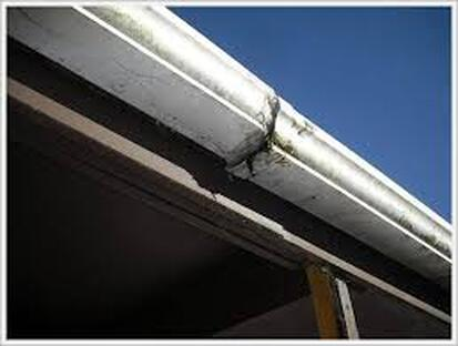 Broken, cracked, and damaged gutters in need of replacing on the roof of a house.